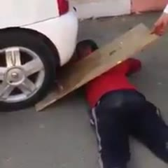 Dumbass almost gets his head crushed by his friend's car